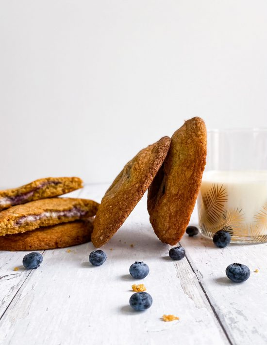 Blueberry Cheesecake Stuffed Cookies Staked Against Glass of Milk - www.foodnerd4life.com