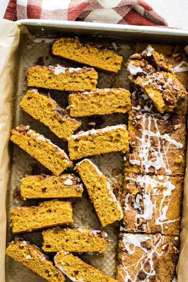Slices of pumpkin coffee cake drizzled with frosting.