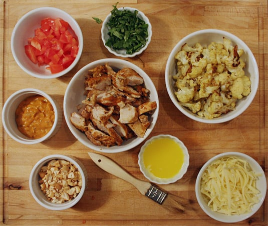 A selection of toppings to make an Indian Tandoori Chicken, Roasted Curried Cauliflower and Cashew Pizza