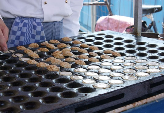 Poffertjes, miniature Dutch pancakes, are made on a special cast iron griddle punctuated by dozens of shallow rounds cups. The mini-pancakes must be turned by hand with a fork before they're ready to be enjoyed.