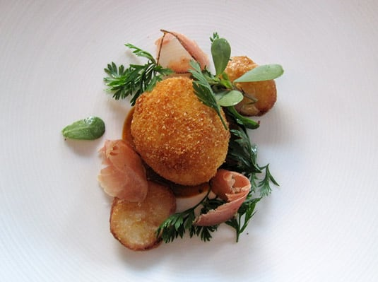 Crispy slow-cooked egg with cured ham, fried potatoes and greens at La Laiterie.