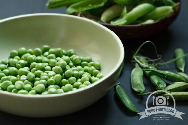 Plate of fresh peeled peas on black table. Rustic style