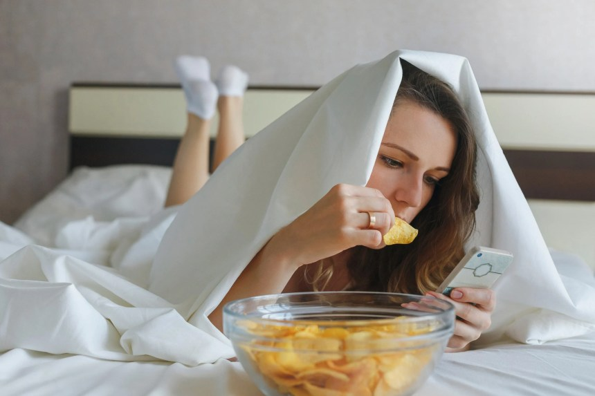 A woman lying in bed on her stomach looking at her phone and eating potato chips while under the covers