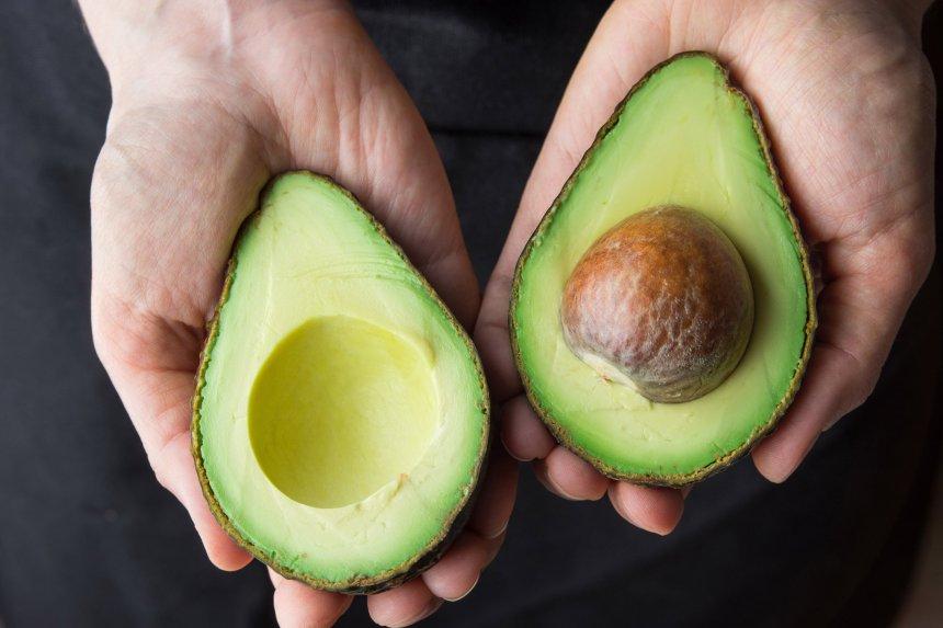 A cut in half avocado in hands