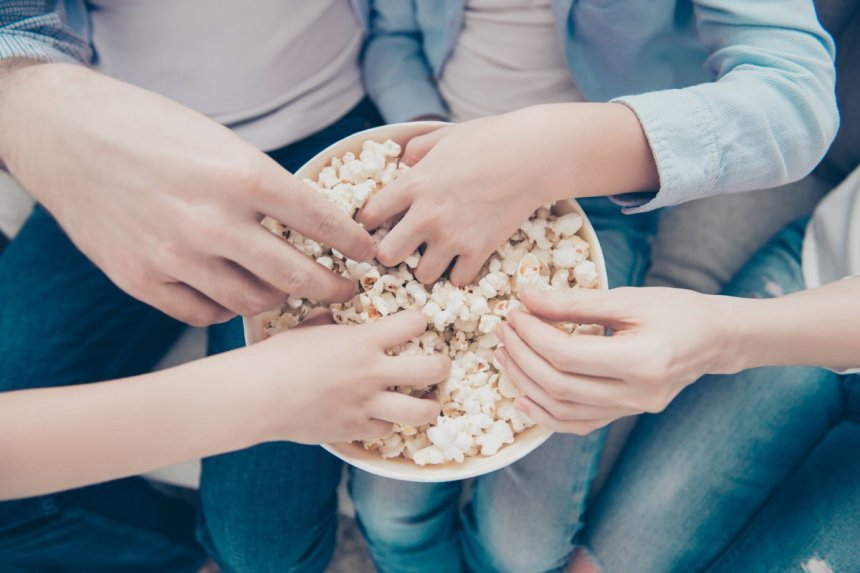Hands in a bowl of popcorn