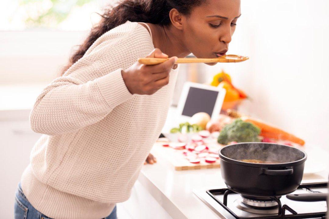 女人用木勺品嚐湯