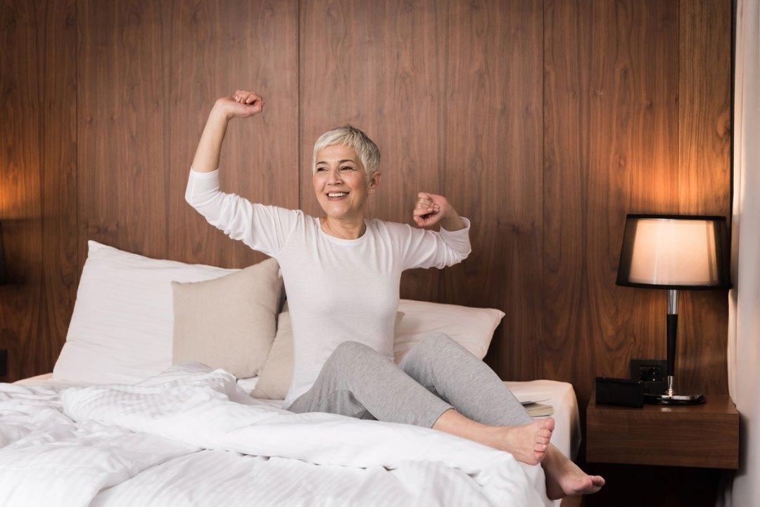 女人睡好後躺在床上伸展