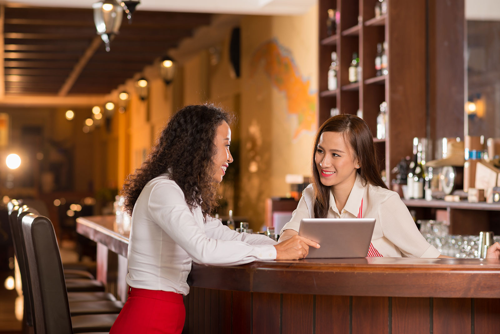 Female restaurant manager showing tablet device screen to waitress standing behind restaurant bar