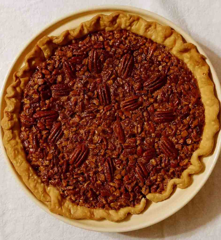 A whole Pecan Pie in a ceramic pie plate