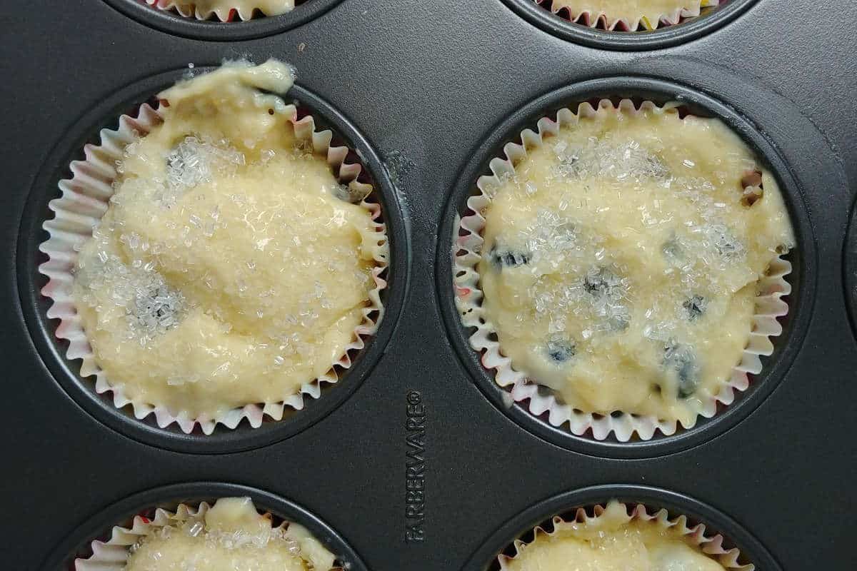 batter for perfect blueberry muffins, in muffin liners, with sugar sprinkled on top
