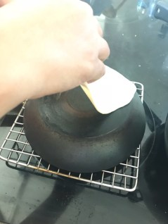 Heat an inverted pan/griddle on the stove-top and keep the rolled naan on pan with wet side down
