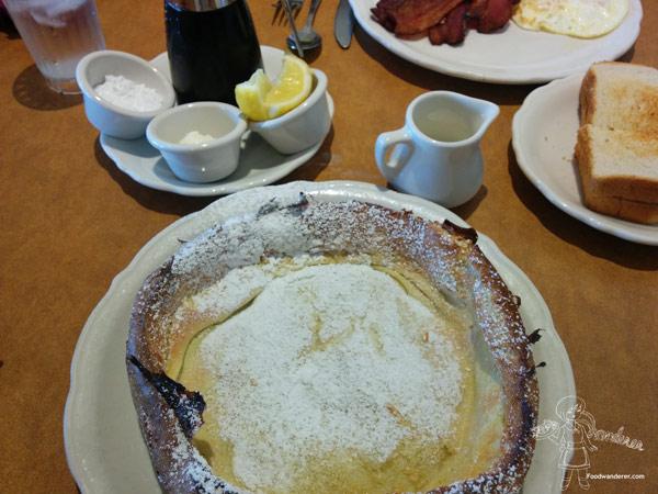 Dutch Baby, lemon wedges and powdered sugar