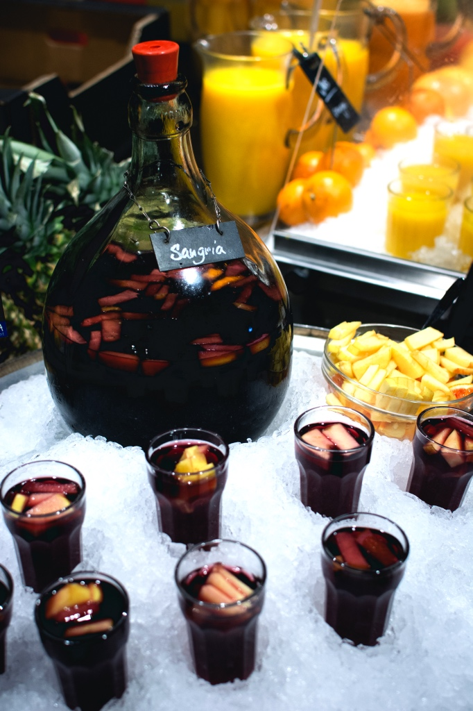 pitcher of sangria and glasses with fresh fruit on ice