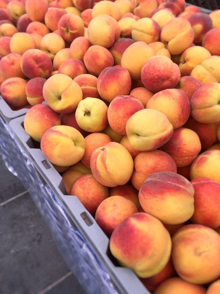 bushels of fresh peaches at the farmers market | local farm share on foodwithaview.com