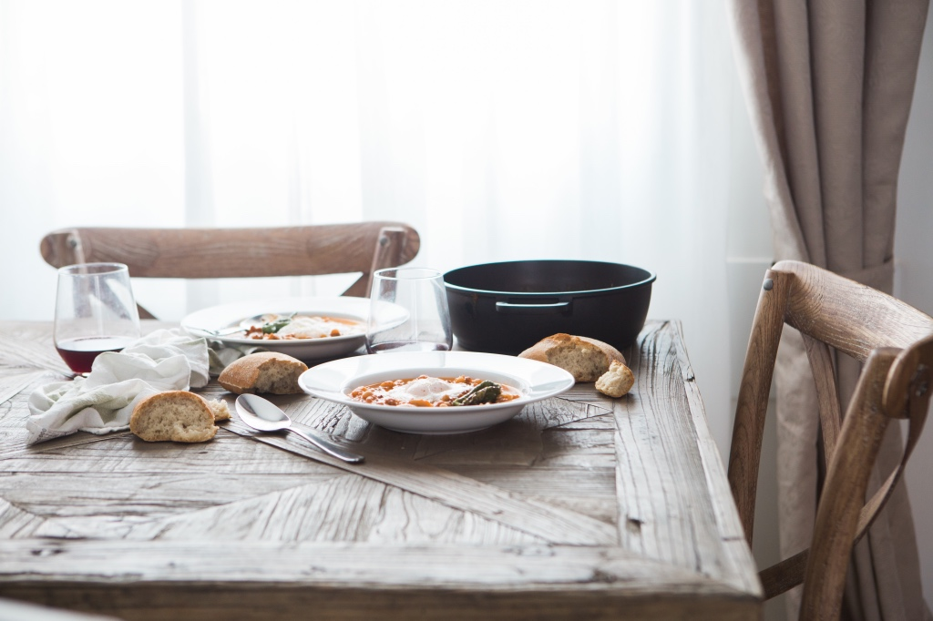 Date night at home: simple soup dinner set for two at a rustic wooden table.
