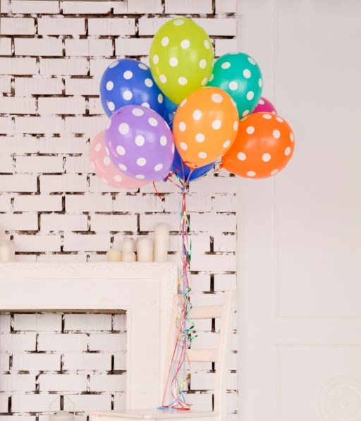 Rainbow polka dot balloons by the fireplace | planning a baby shower on foodwithaview.com | photo by sofiya levchenko