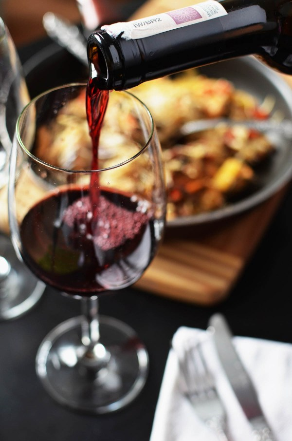 Pouring a glass of red wine for Thanksgiving dinner | Thanksgiving Turkey and Wine Pairings | foodwithaview.com