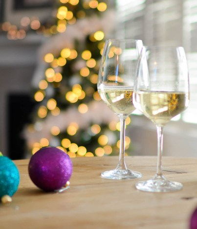 Glasses of white wine with holiday decorations | Holiday Food and Wine Pairings and Holiday Wine Gifts | foodwithaview.com