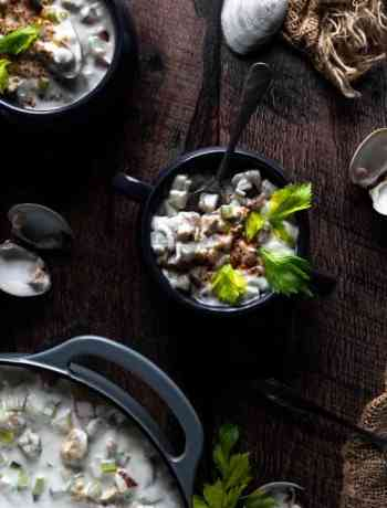 Overhead photo of New England Clam Chowder garnished with paprika and celery leaves.