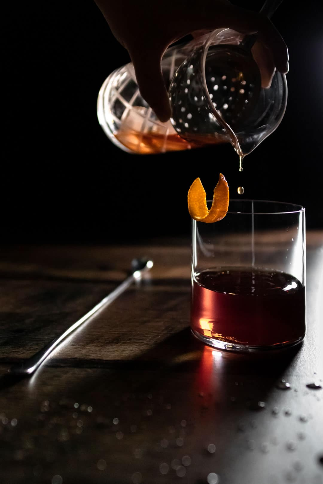 amaro old fashioned being poured into glass