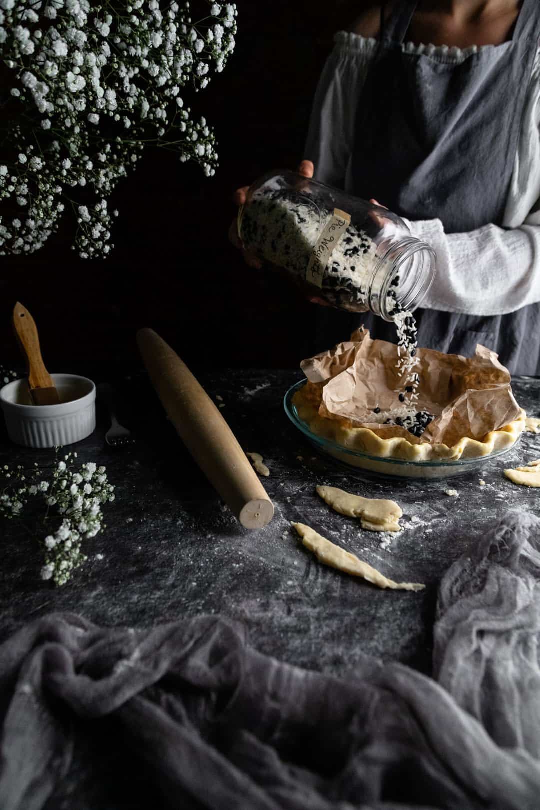 A woman pouring dried rice and beans from a jar into the coffee-filter lined unbaked pie crust. She is preparing the pie crust for blind baking.