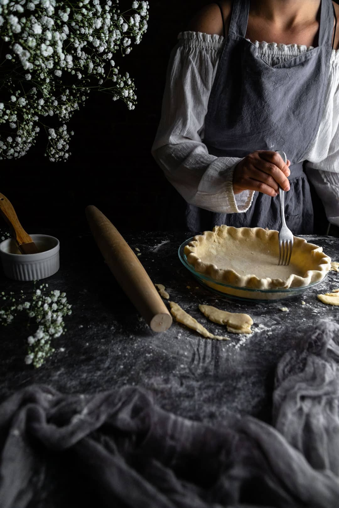 A woman using a fork to poke holes (dock) the bottom of an unbaked crimped pie crust next to a rolling pin and vase of tiny white flowers