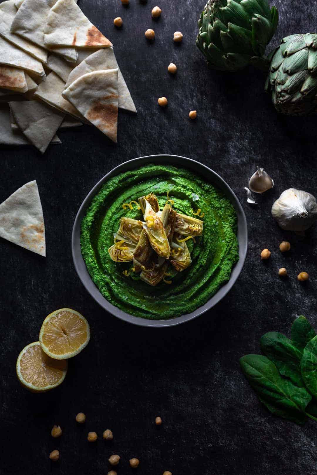 Spinach hummus scene with pita triangles, lemons and garlic