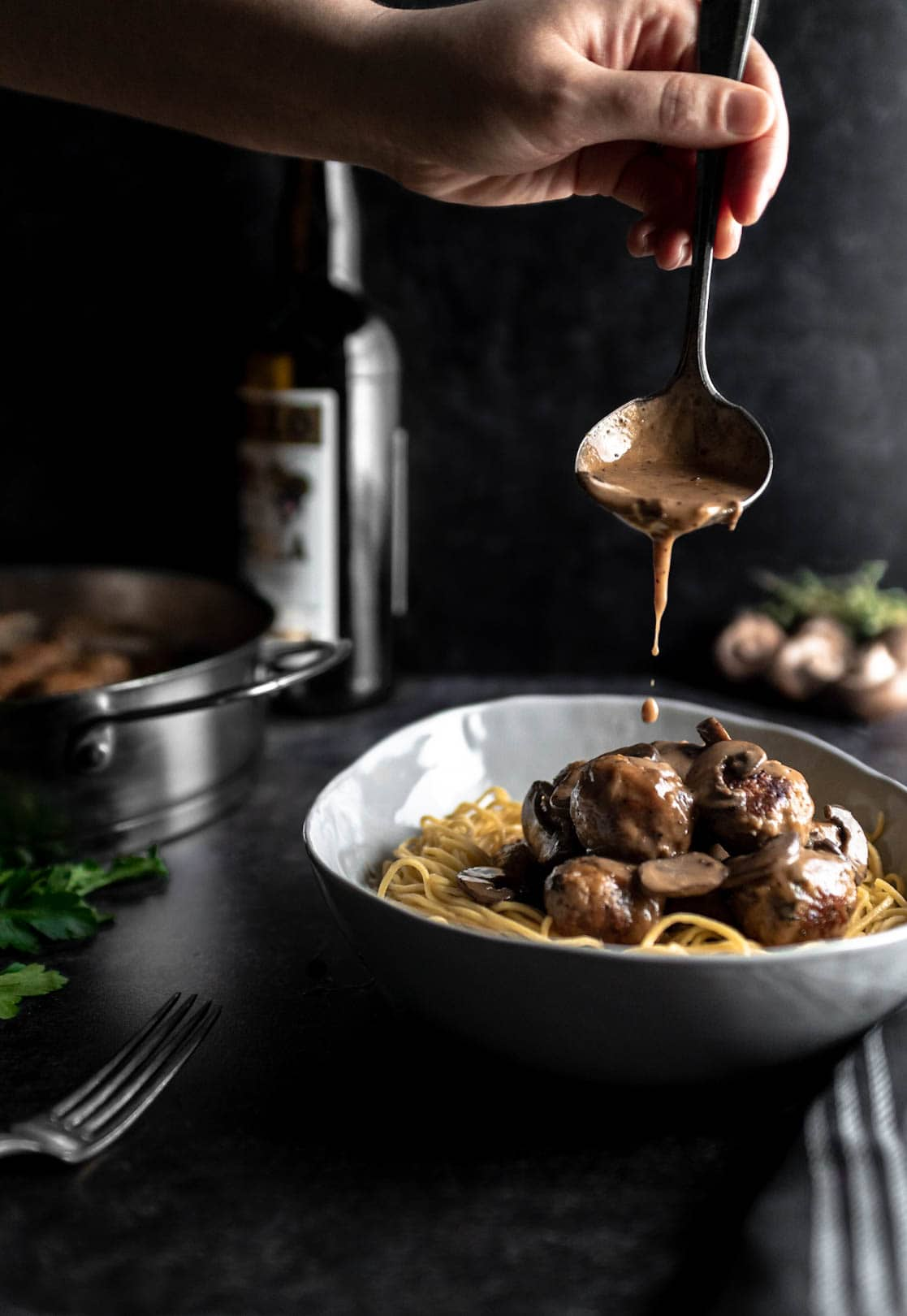 Marsala cream sauce being poured over chicken mushroom meatballs