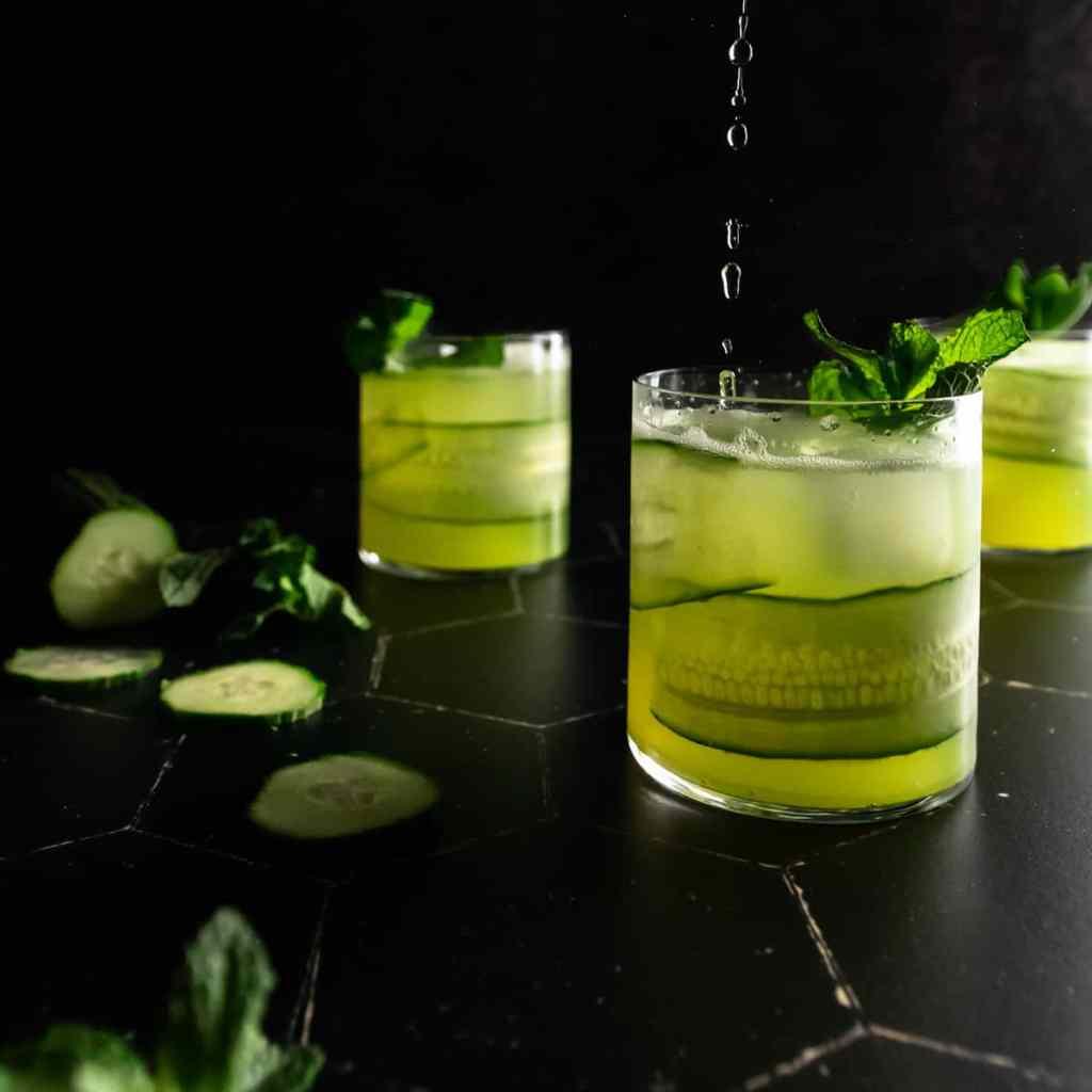 Pouring soda water into a cucumber mojito