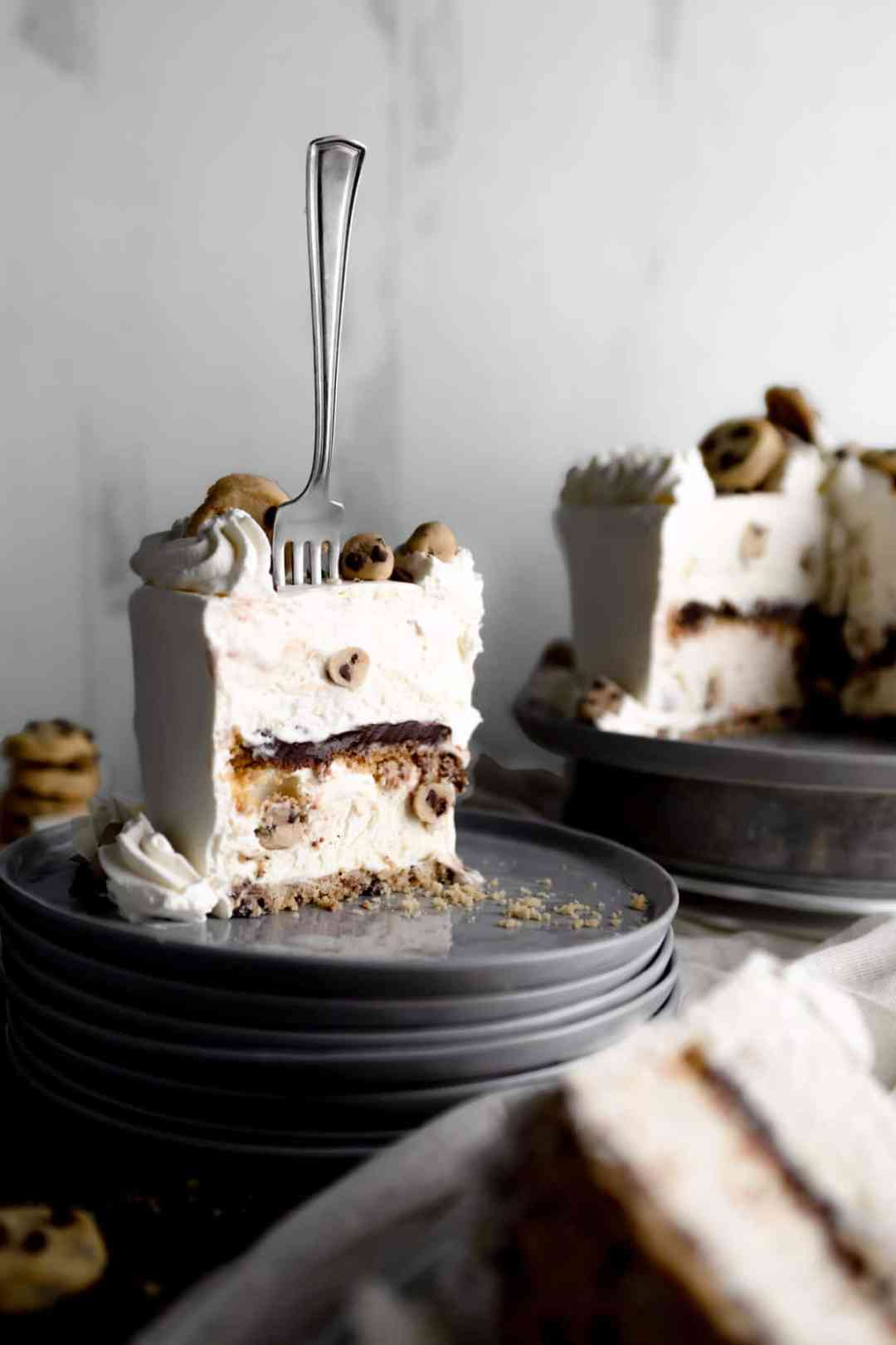 A fork standing in a slice of Cookie Dough Ice Cream Cake