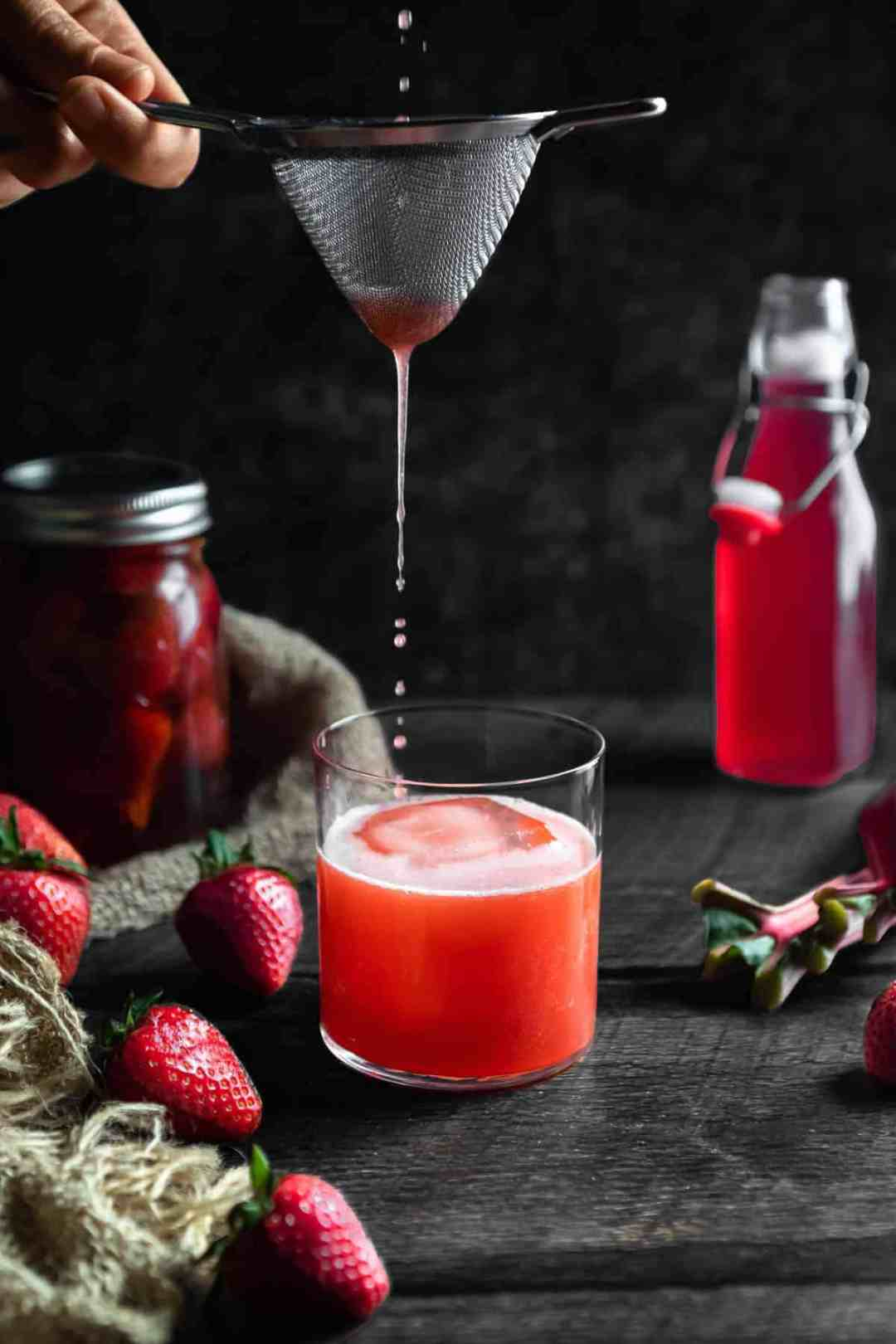 Strawberry Whiskey Sour Being poured into a glass through a strainer