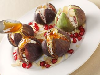 Fresh figs stuffed with mizithra sheep's cheese and toasted almond slivers, topped with honey and garnished with pomegranate seeds, seen from above.