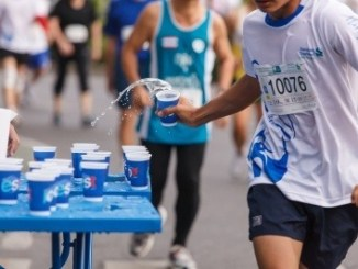 Marathon runners collecting cups of water (photo)
