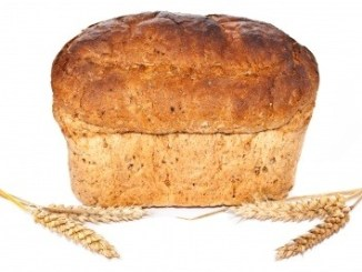 Brown bread load with some wheat heads on a white background. We wish we could smell the flavour of bread in a photo.
