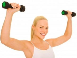 A beautiful woman exercising with dumb bells.