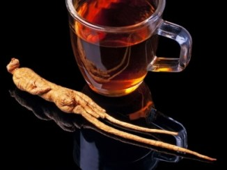 Ginseng tea on a black background with a root of ginseng.