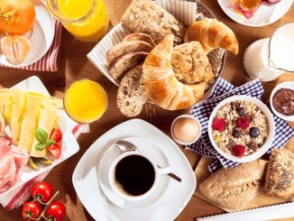 top view of coffee, juice, fruit, bread and meat on table. Breakfast.