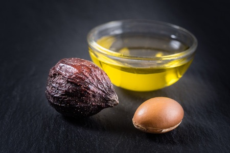 46093488 - argan oil and fruits on a black background.