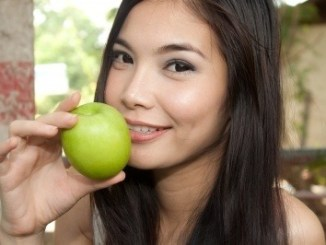 Beautiful girl about to chomp on a green apple.