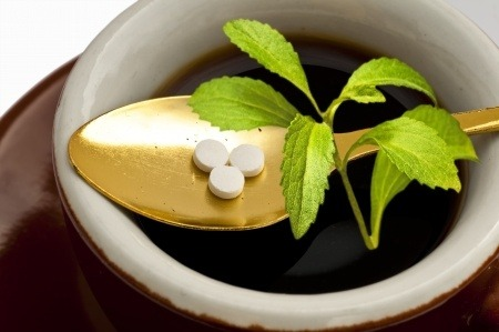 Stevia pills and stevia plant on a golden spoon in a bowl.