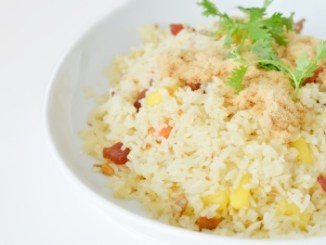 A mixed vegetable rice dish with a sprg of green herb on top, in a white bowl on a white background.