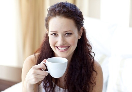 Beautiful girl, smiling, looking face on, holding a white cup of coffee