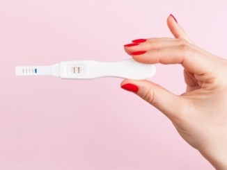 41890595 - beautiful female hand with red fingernails holding positive pregnancy test isolated on pink background. motherhood, pregnancy, birth control concept. minimal sparse modern image language.