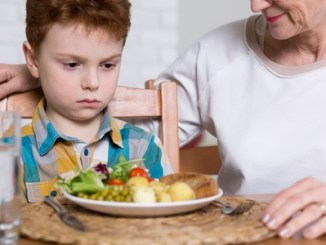 Close-up of a little boy looking malevolently at a dinner plate full of healthy food with his mother looking kindly on.
