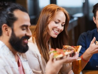 Smiling friends eating pizza and drinking beer at restaurant or pub