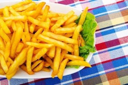 French fries with lettuce on a white plate, on a plaid tablecloth.. One of the foods associated with acrylamide formation.