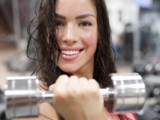 Beautiful woman doing a handbell curl. Looking sweaty.