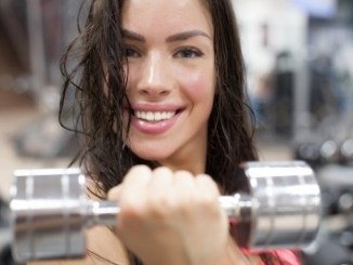 Beautiful woman doing a handbell curl. Looking sweaty.. Whey protein isolate might be one of the ingredients she takes for a her gym work.