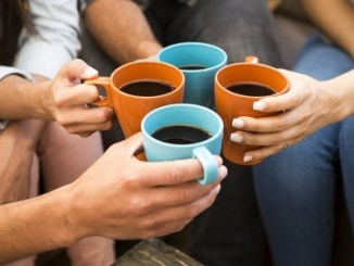 A group of friends making a toast with coffee.