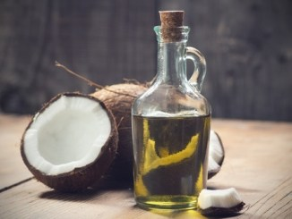 A bottle of coconut oil with some broken coconuts around it.